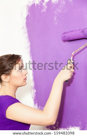 Girl painting wall with purple paint