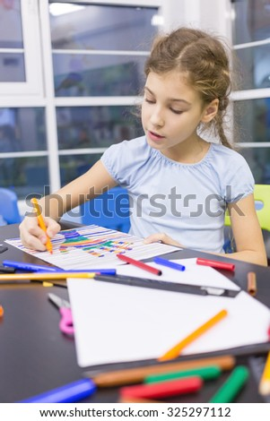 girl paints a felt pen drawing of hand - stock photo