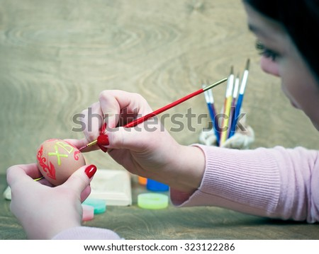 Girl paints easter egg