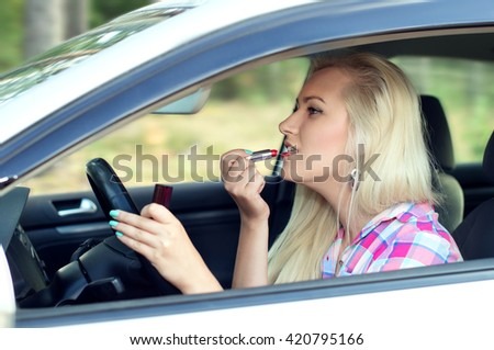 Girl paints her lips at the wheel of a car while driving