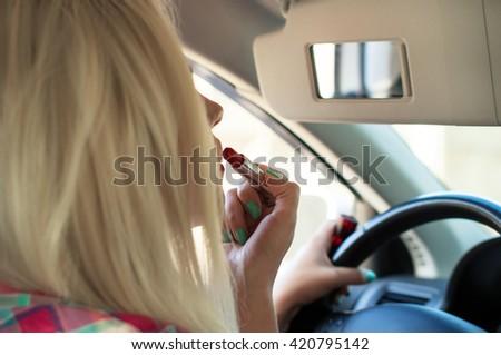 Girl paints her lips at the wheel the car