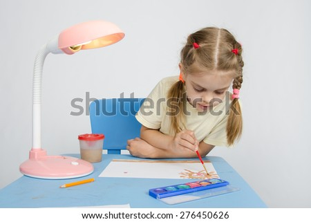 Girl paints sitting at the table