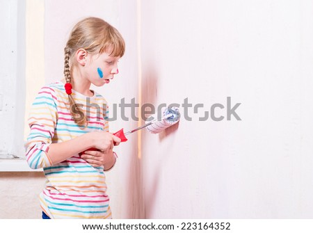girl paints the wall roller