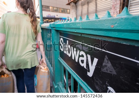 Girl passing in front of a Subway entrance in New York City. - stock photo