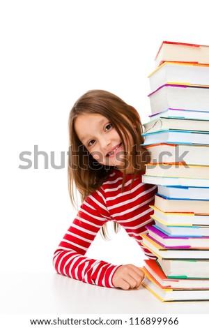 Girl peeking behind pile of books on white background - stock photo