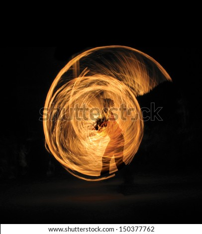 Girl performing fire dance in the night; silhouette - stock photo