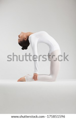 girl performs yoga in white studio