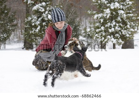 Girl petting her little dogs in the winter snow - stock photo