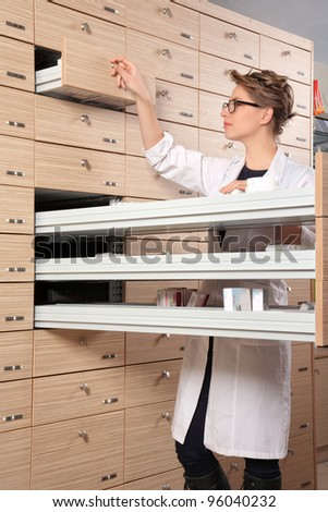girl pharmacist portrait in front of drawers - stock photo