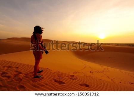 Girl Photographer in Sunrise Desert  - stock photo