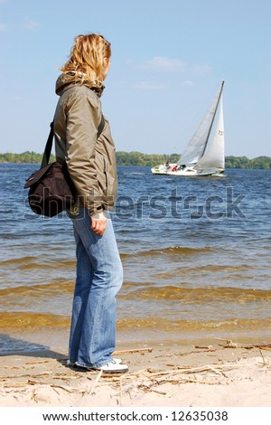 Girl-photographer looking to the white yacht at the river - stock photo