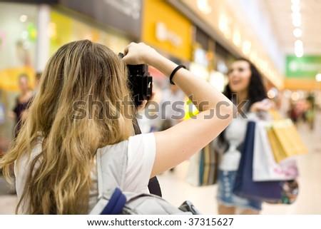 girl photographer shoot model in mall - stock photo