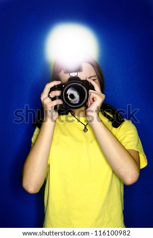 Girl photographer taking photo with digital camera and flash - stock photo