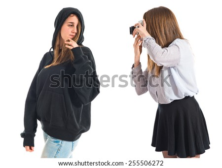 Girl photographing at her twin sister