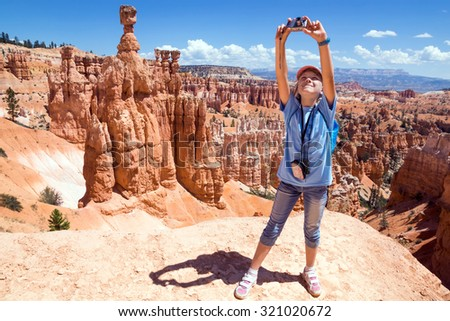 Girl photographs on the camera mountain landscape. Bryce Canyon National Park, Utah, United States