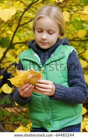 Girl picking colorful leaves in autumn park - stock photo