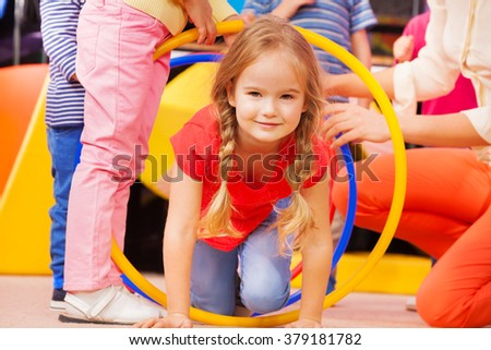 Girl play a game in kindergarten crawl though hoop - stock photo