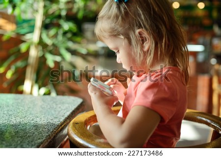 girl play phone in cafe during waiting food - stock photo