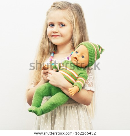Girl play with baby doll. Mothers day concept. Isolated portrait. - stock photo