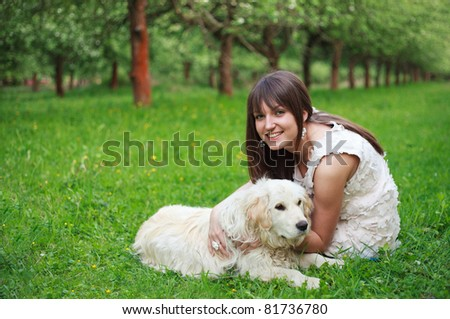 Girl play with golden retriever in park - stock photo