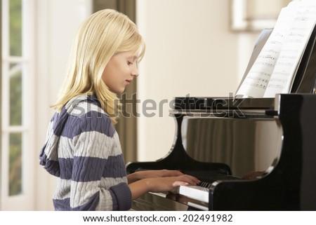 Girl playing grand piano at home - stock photo