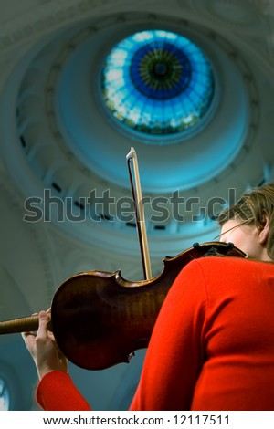 Girl playing her violin at the symphony concert - stock photo
