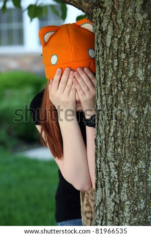 girl playing hide and go seek in hat by tree - stock photo