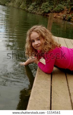 Girl playing in lake water - stock photo