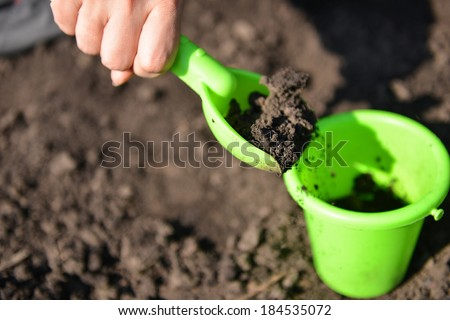 Girl playing in the mud with green toy bucket and spade - stock photo