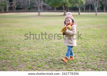 Girl playing in the park with a teddy bear - stock photo