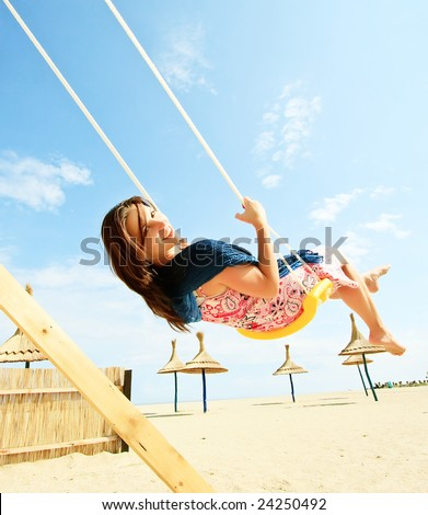 Girl playing on a swing-set on the beach