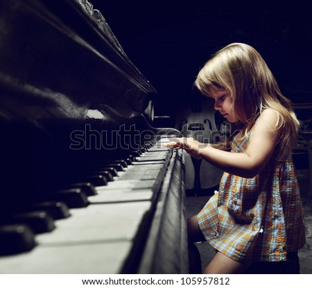 girl playing on an old black piano - stock photo
