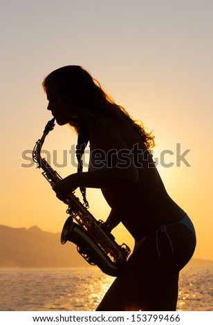 Girl playing on saxophone against the background of sunset