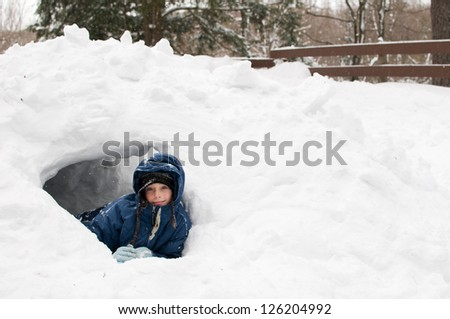 girl playing outdoors in a snow fort on a winters day - stock photo