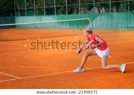 Girl playing tennis outdoor on court - stock photo