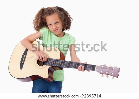 Girl playing the guitar against a white background