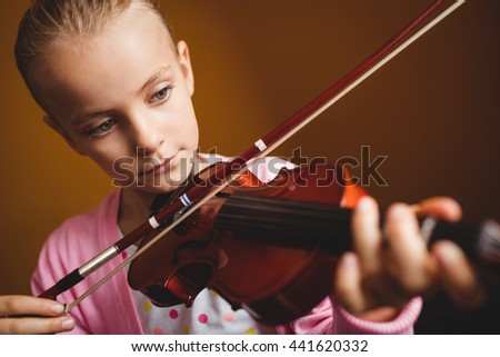 Girl playing the violin on yellow background