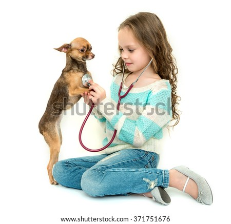 Girl playing veterinarian with dog, isolated on white. - stock photo