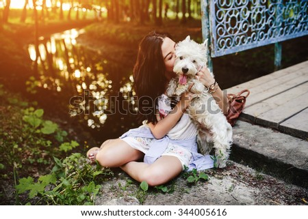 girl playing with a dog on the bank of the river near the bridge - stock photo