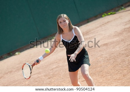 Girl playing with a tennis racquet on a tennis court for lessons. - stock photo