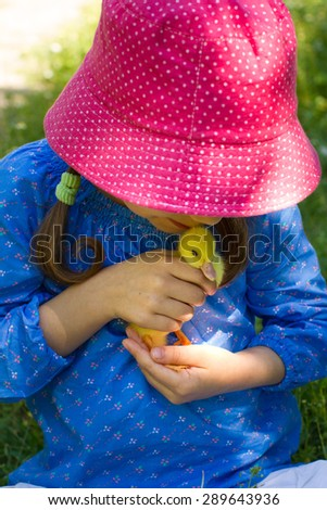 Girl playing with baby duck - stock photo