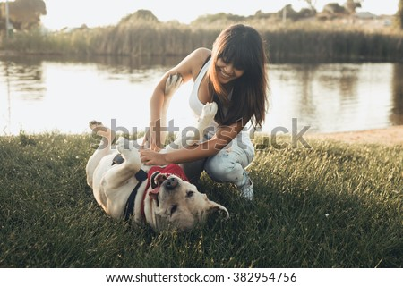 Girl playing with dog on grass - stock photo