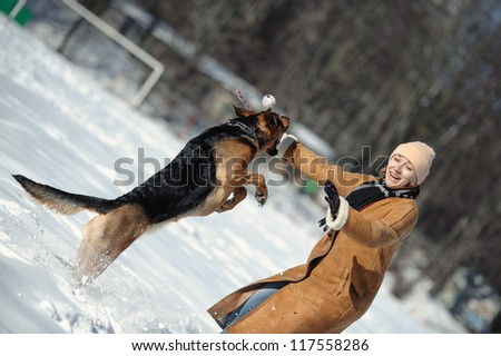 Girl playing with dog on the snow - stock photo