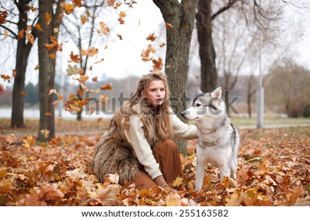 Girl playing with her husky dog in the park, autumn. Fashion blonde stylish woman.