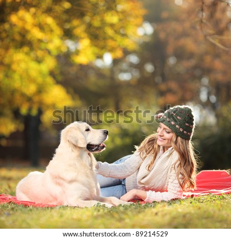 Girl playing with her labrador retriever dog in the park - stock photo