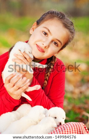 Girl playing with her puppies in the park - stock photo