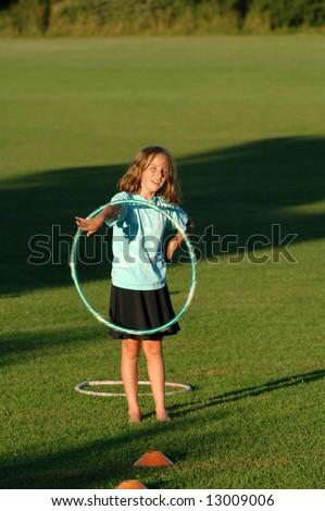girl playing with hula hoop at park - stock photo