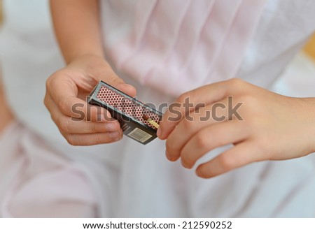 Girl playing with matches. Dangerous situation at home. - stock photo