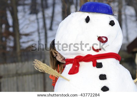 girl playing with snowman