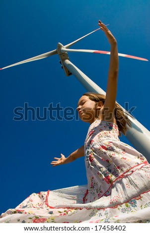 girl playing with the wind under a turbine